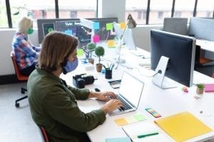 Caucasian business people wearing face masks in creative office
