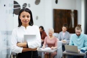 Mixed-Race Teacher Posing by Board