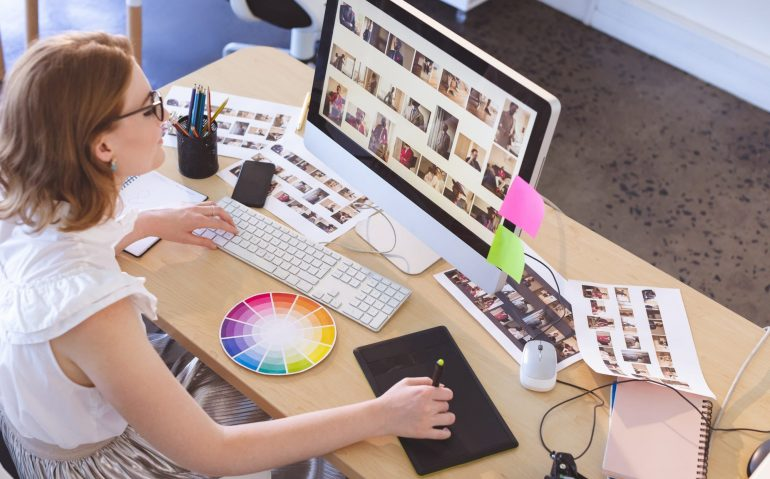Female graphic designer working on graphic tablet and computer at desk