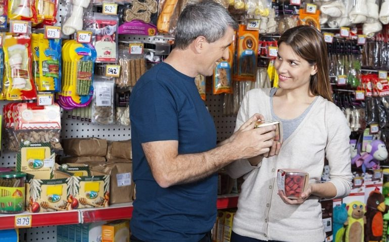 Smiling couple buying pet food in store